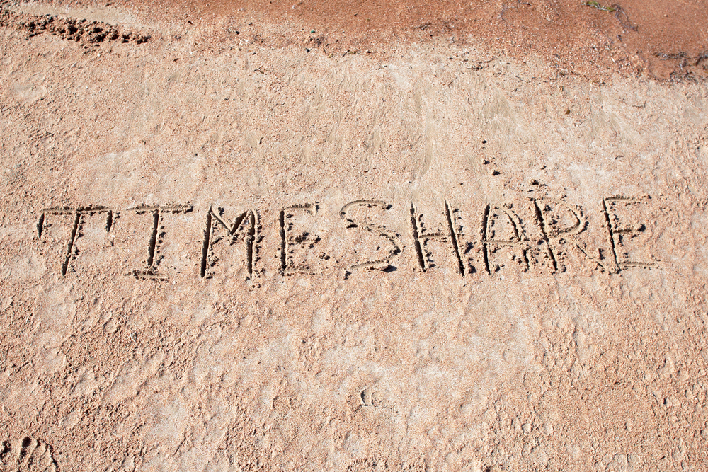 the word timeshare written in sand